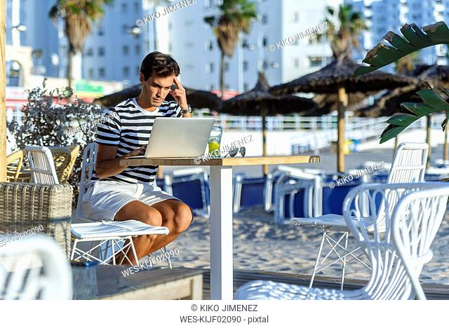 Man with laptop sitting on the terrace of a beach bar