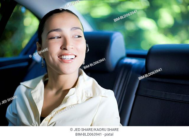 Hispanic businesswoman with hands-free cell phone device