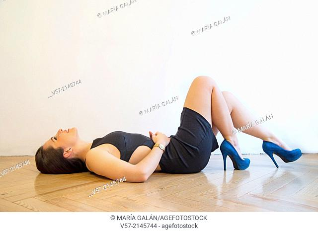 Sexy young woman lying on wooden floor