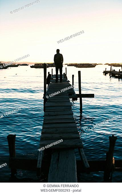 Bolivia, Man standing on wooden boardwalk looking the Titicaca Lake at sunset