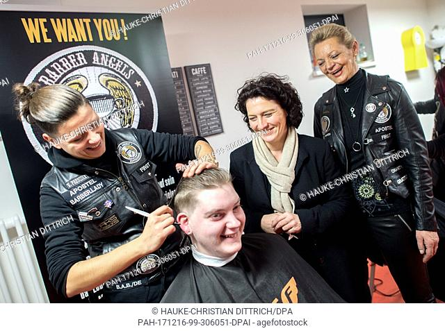 Lower Saxony's Minister for Social Affairs Carola Reimann (2-R) and the ograniser Gaby Guenther (R) have a conversation with Tim (C) who gets a new haircut from...