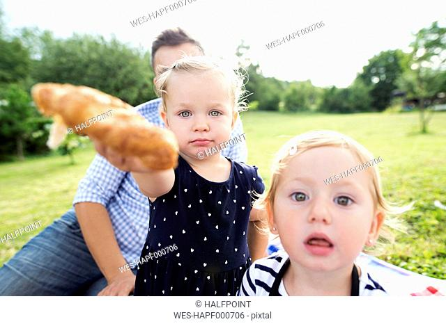 Little girl with father and sister in a park offering croissant to viewer