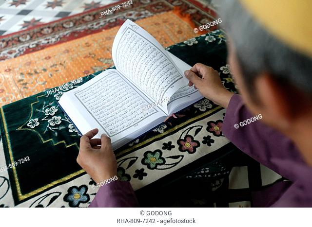 Muslim man reading an Arabic Holy Quran (Koran), Saigon Central Mosque, Ho Chi Minh City, Vietnam, Indochina, Southeast Asia, Asia