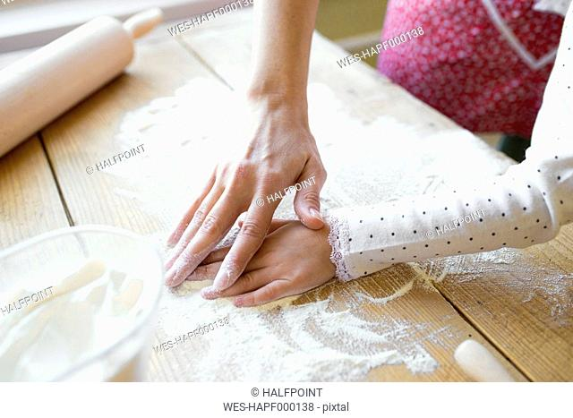 Woman's and her little daughter's hands on table top covered with flour, close-up