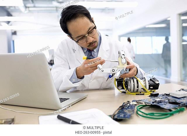 Engineer at laptop assembling robotics at desk