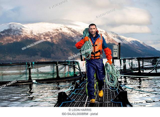 Worker on salmon farm in rural lake