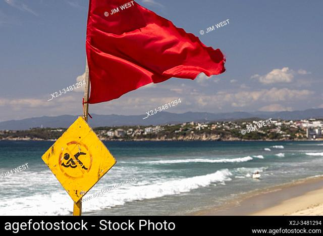 Brisas de Zicatela, Oaxaca, Mexico - The Pacific Ocean beach, looking towards Puerto Escondido. The red flag warns of dangerous swimming conditions
