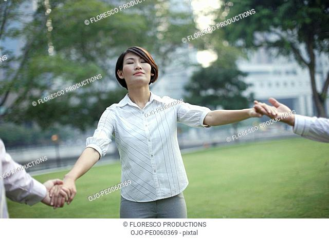Three businesspeople outdoors in park holding hands
