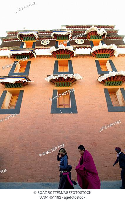Tibetan pilgrims and a monk walking by one of Labrang monastery complex temples
