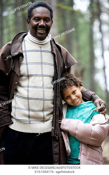 Father and Daughter, young child, enjoy each other's company walking through a forest