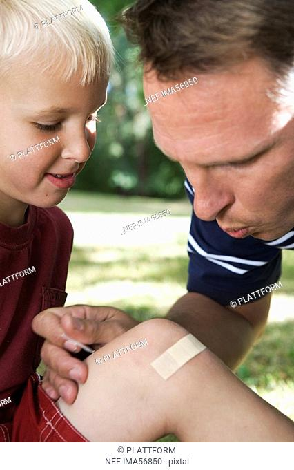 A father putting on a plaster on the knee of his son Sweden