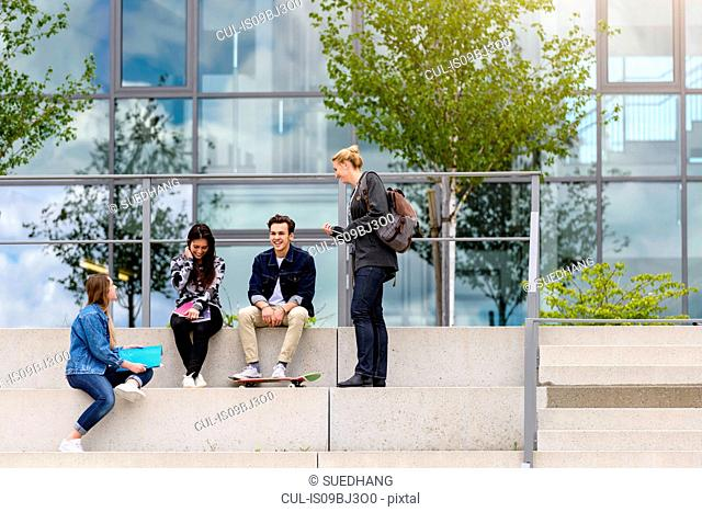 Four young adult students sitting chatting on stairway outside college