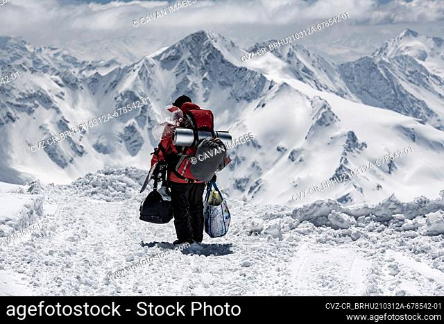 Rear view of male hiker carrying bags while walking on snow covered mountain during vacation
