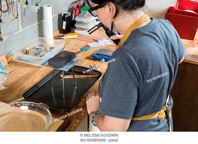 Jewellery maker, making jewellery in workshop
