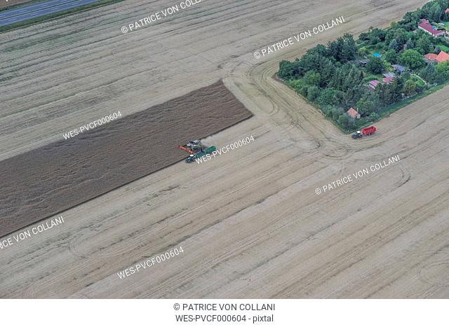 Germany, aerial view of combine harvester at work on a field