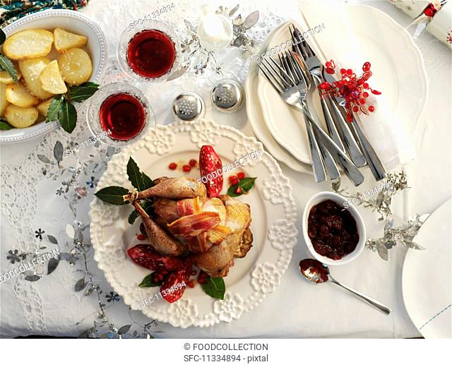 Roast pheasant wrapped in bacon with pomegranate seeds and potatoes for Christmas