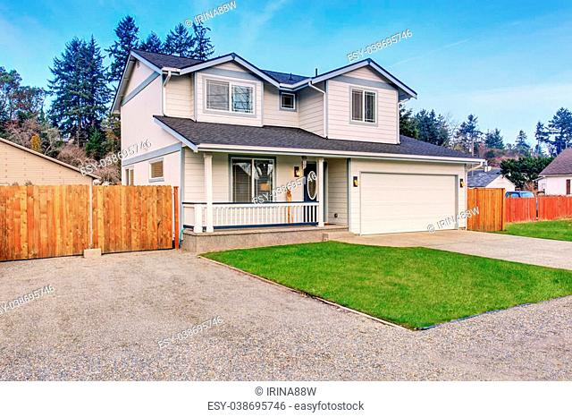 Traditional northwest home with driveway, grassy areas, and a garage