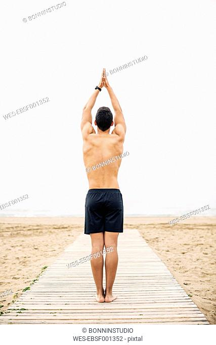 Young man practicing yoga on boardwalk on the beach
