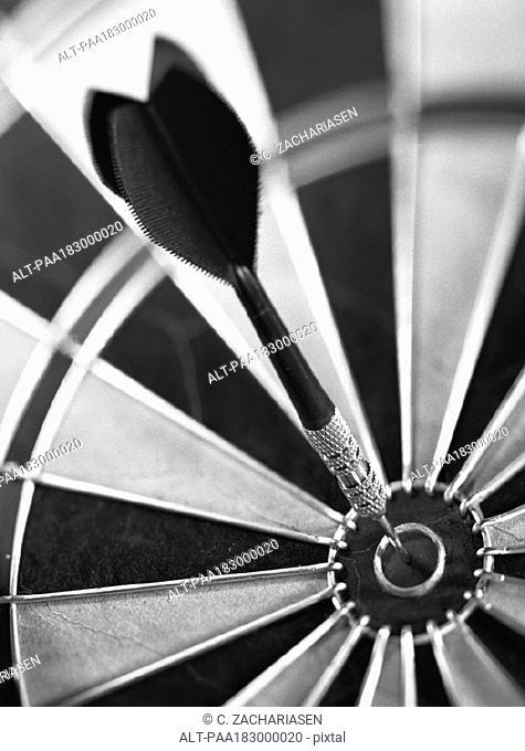 Dart in center of dartboard, close-up, b&w
