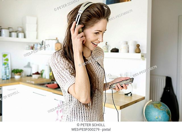 Happy young woman in kitchen listening to music