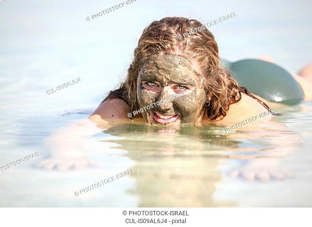 Mud covered female tourist floats in the Dead Sea, Israel