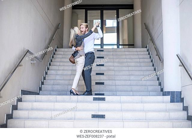 Businesswoman and man dancing on stairs