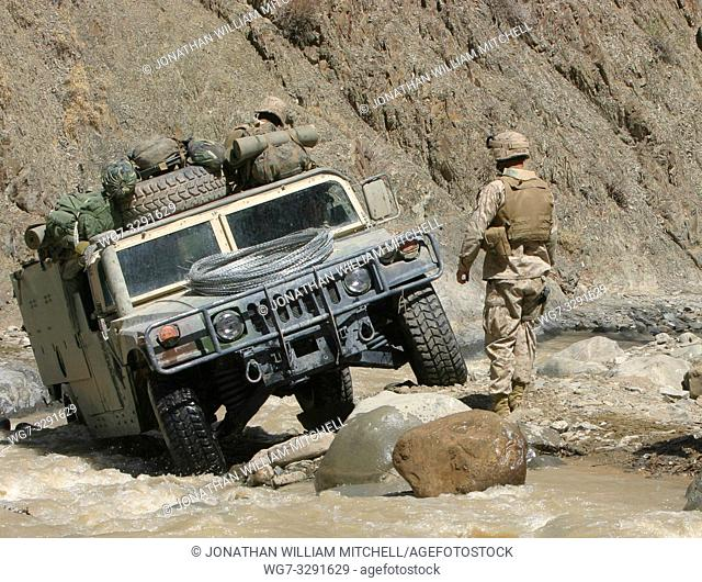AFGHANISTAN Khost Province -- 28 Mar 2005 -- A US Marine ground guides the driver of a Humvee through a river as they negotiate through the rugged terrain of...