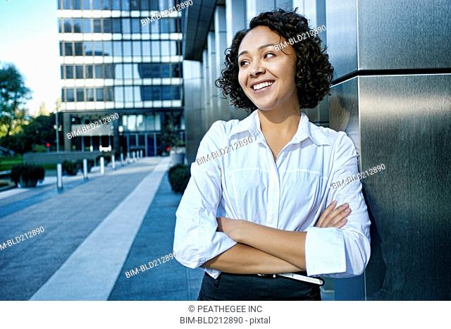 Mixed race businesswoman standing in city