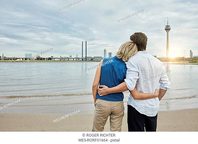 Germany, Duesseldorf, affectionate young couple at Rhine riverbank