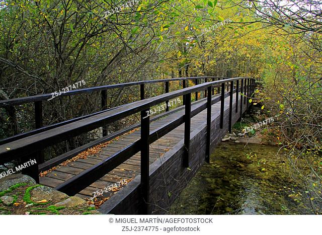 A pedestrian bridge crosses over the young Lozoya river close to the man made river pools of Las Presillas, near the monastery of El Paular (Madrid autonomous...