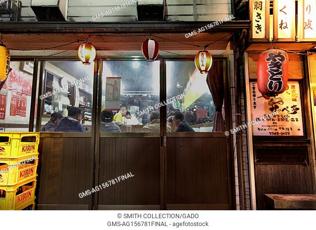 People are visible dining in a small restaurant, through a window, in the Omoide Yokocho (Memory Lane) area of Shinjuku, Tokyo, Japan at night