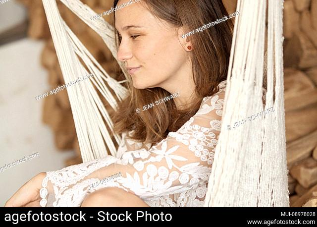 young woman sits in hammock