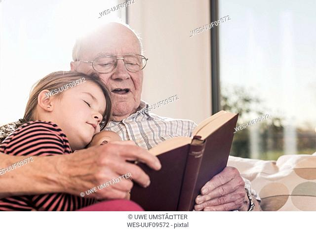 Grandfather reading out story for his granddaughter