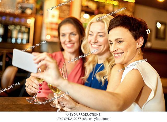 women taking selfie by smartphone at wine bar