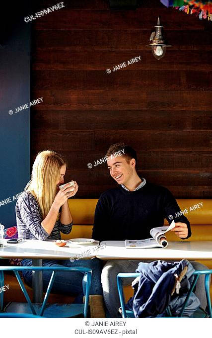 Young couple on date in cafe drinking coffee and reading magazine
