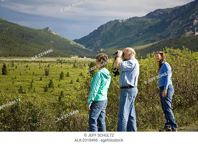 Mature Couple And Middle Age Woman Hike On Tundra In The Sanctuary River Area Of Denali National Park, Alaska