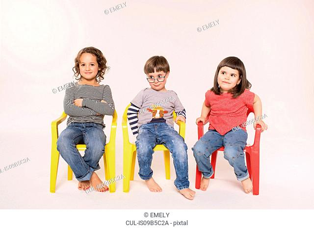 Portrait of three children sitting in colourful chairs, studio shot