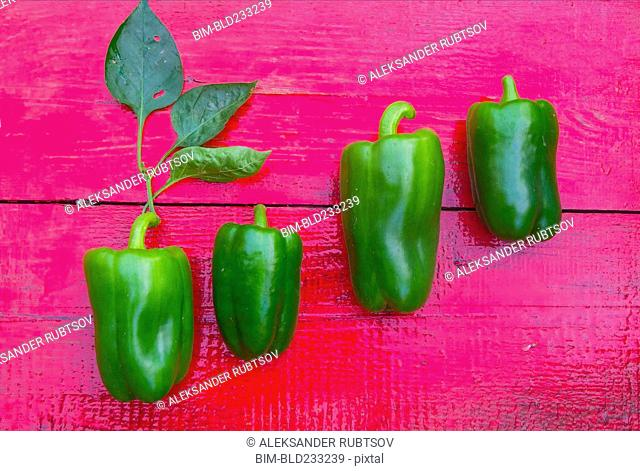 Close up of row of green peppers on red wooden table