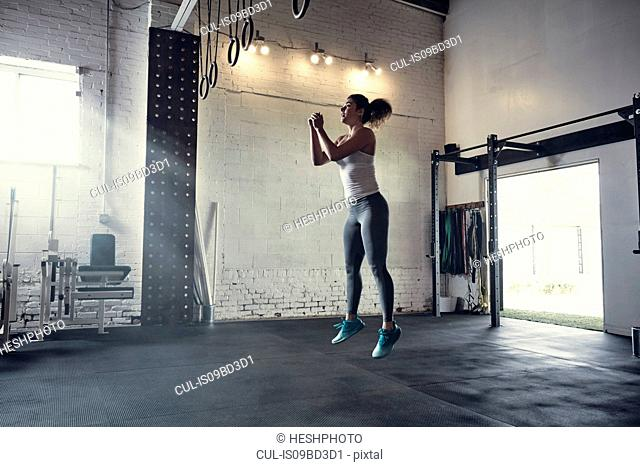 Woman in gym jumping in mid air