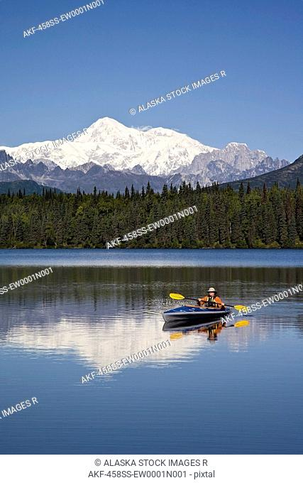 Man paddling a Klepper kayak on Byers Lake at Denali State Park. Mt. McKinley is visible in the background. August. Summer in the interio of Alaska
