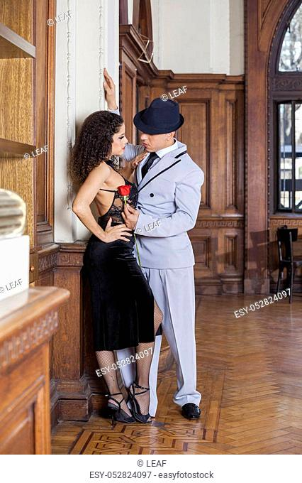 Full length of young tango dancer holding rose while looking at female partner in restaurant