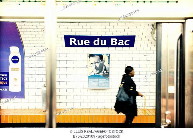 view of a unrecognizable woman walking down the platform of the subway station Rue du Bac, Paris
