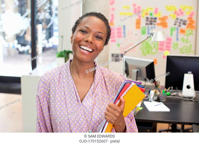 Portrait of confident businesswoman holding paperwork in office