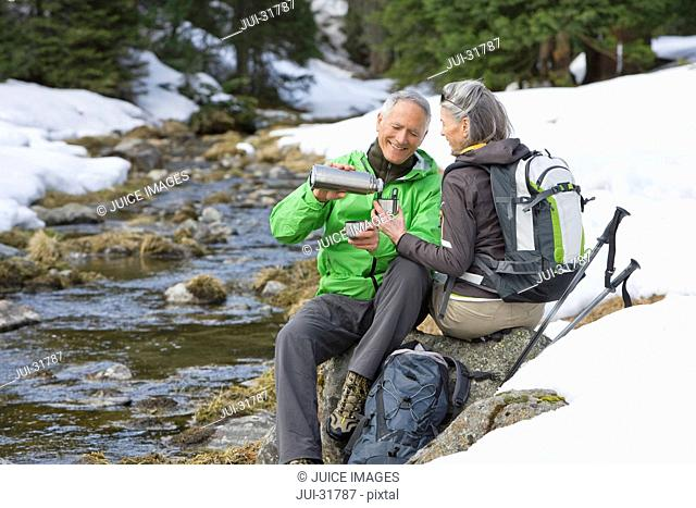 Man pouring coffee for woman at edge of stream in snowy woods