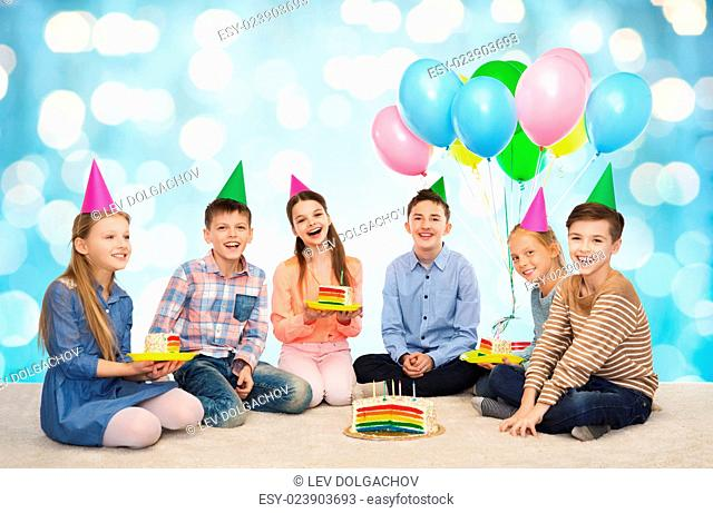 childhood, holidays, celebration, friendship and people concept - happy smiling children in party hats with birthday cake and balloons over blue holidays lights...