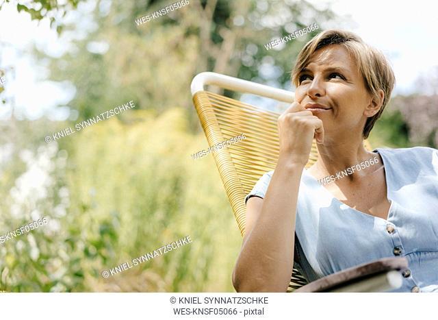 Portrait of woman sitting in garden on chair