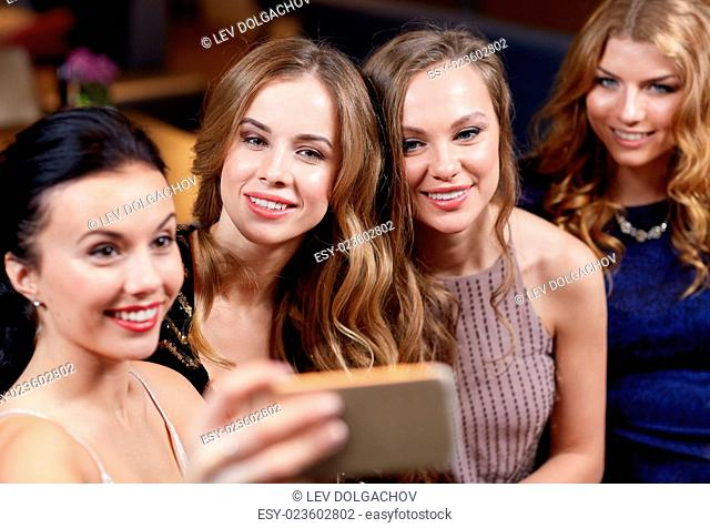 celebration, friends, bachelorette party, technology and holidays concept - happy women with smartphone taking selfie at night club