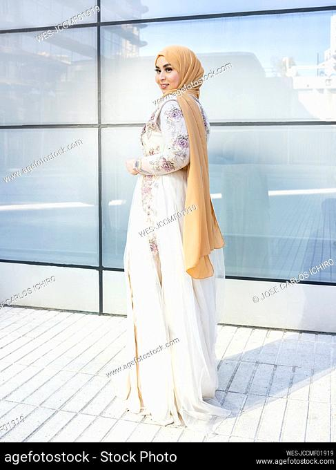 Young fashionable woman wearing hijab and dress standing on footpath