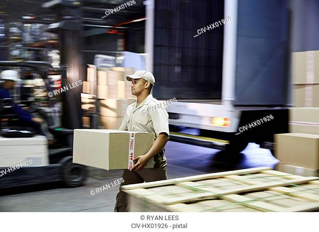 Worker carrying cardboard box at distribution warehouse loading dock