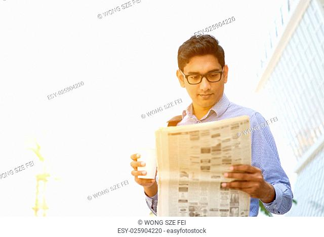 Asian Indian business people holding coffee cup and reading newspaper on the way to work place in morning. Handsome male model